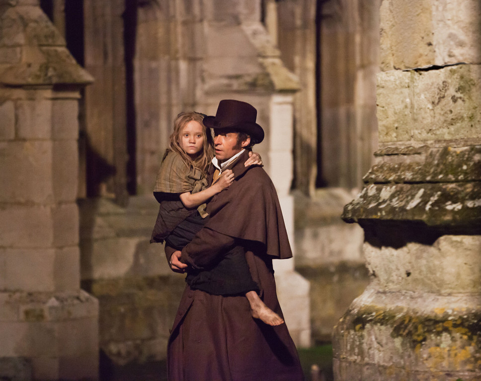 ". This undated publicity image provided by Universal Pictures shows Isabelle Allen, left, as a young Cosette and Hugh Jackman as Jean Valjean in a scene from the motion-picture adaptation of ""Les Mis�rables,î directed by Tom Hooper. (AP Photo/Universal Pictures, Laurie Sparham, File)-"