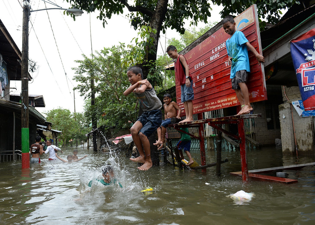 . Boys affected by flooding due to heavy rains exarcebated by Tropical storm Trami play on a flooded street in the town of Calumpit, Bulacan province, north of Manila on August 22, 2013. Disaster-weary Philippine residents mopped up August 22 after four days of rains that officials said had killed 18 people and forced more than half a million from flooded homes. TED ALJIBE/AFP/Getty Images
