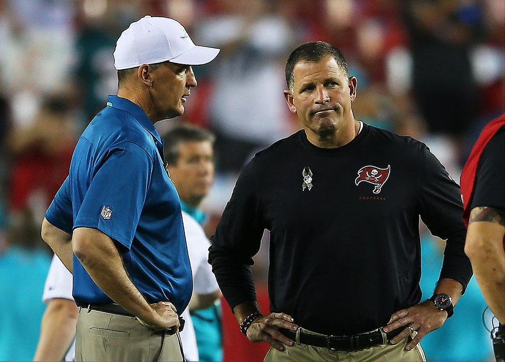 . TAMPA, FL - NOVEMBER 11:  Head coach Joe Philbin (L) of the Miami Dolphins talks to head coach Greg Schiano of the Tampa Bay Buccaneers prior to their game at Raymond James Stadium on November 11, 2013 in Tampa, Florida.  (Photo by Mike Ehrmann/Getty Images)