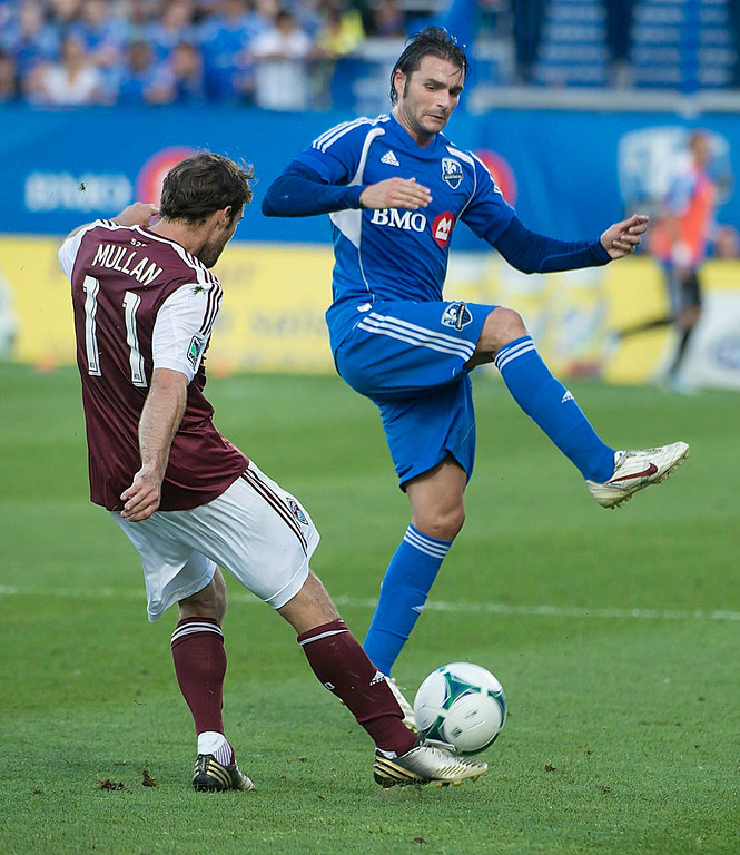 . Montreal Impact\'s Andrea Pisanu, right, tries to block the pass by Colorado Rapids\' Brian Mullan during the first half of an MLS soccer in Montreal on Saturday, June 29, 2013. (AP Photo/The Canadian Press, Peter McCabe)