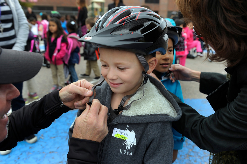 . DENVER, CO - Oct. 11: Kindergartener Adam Urquidi, 6, gets fitted with a new helmet. Wish for Wheels and its volunteers build and give away over one hundred bikes to kindergarteners and first-graders at Smith Renaissance School in Park Hill. Wish for Wheels says its goal with one-in-five children liven in poverty, is to give as many kids as possible their first brand new bike and helmet. (Photo By Kathryn Scott Osler/The Denver Post)