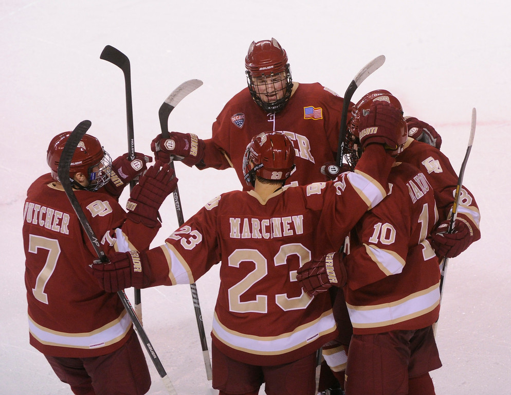 . DENVER, CO. - OCTOBER 25: Denver wing Ty Loney (12) celebrated a goal with teammates Will Butcher (7) Matt Marcinew (23) David Makowski (10) and Trevor Moore (8) in the second period. The University of Denver hockey team hosted Niagara at Magness Arena Friday night, October 25, 2013. Photo By Karl Gehring/The Denver Post