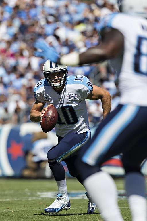 . Jake Locker #10 of the Tennessee Titans rolls out of the pocket and looks downfield for a receiver against the San Diego Chargers at LP Field on September 22, 2013 in Nashville, Tennessee.  The Titans defeated the Chargers 20-17.  (Photo by Wesley Hitt/Getty Images)