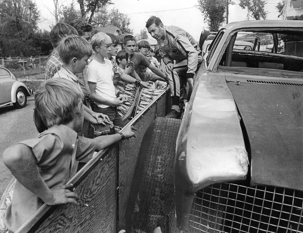 . A group of Denver Post carrier-salesmen listen with interest as race driver Larry DeChant, right, explains the structure of his stock car. More than 125 of the young news paper boys will be guests Sunday of the Century 21 International Speedway, located east of Aurora, for the Late Model, Short Track World Championship race. September 4. 1971. (Photo by Barry Staver/The Denver Post Archive)