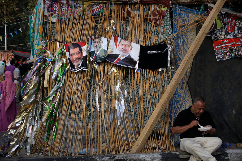 """. A supporter of Egypt\'s ousted President Mohammed Morsi eats under his posters at Nahda Square, where protesters have installed their camp near Cairo University in Giza, southwest of Cairo, Egypt, Saturday, Aug. 10, 2013. The Arabic reads, \""""Yes for legitimacy.\"""" (AP Photo/Amr Nabil)"""
