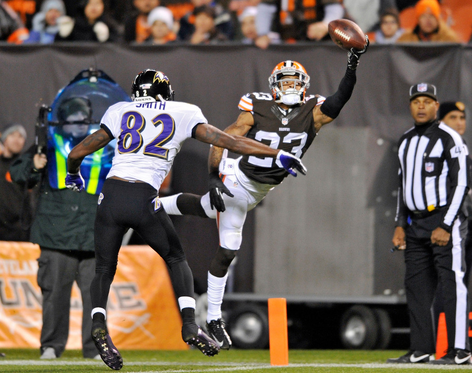 . Cleveland Browns cornerback Joe Haden (23) tips a pass away from Baltimore Ravens wide receiver Torrey Smith (82) in the end zone in the second quarter of an NFL football game Sunday, Nov. 3, 2013. (AP Photo/David Richard)