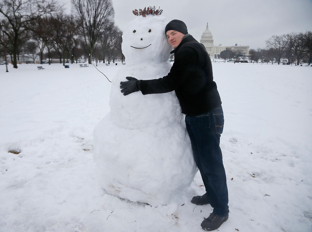 . Larry Gard from Chicago hugs a snowman he just built on the National Mall in Washington, Thursday, Feb. 13, 2014. After pummeling wide swaths of the South, a winter storm dumped nearly a foot of snow in Washington as it marched Northeast and threatened more power outages, traffic headaches and widespread closures for millions of residents. (AP Photo/Charles Dharapak)