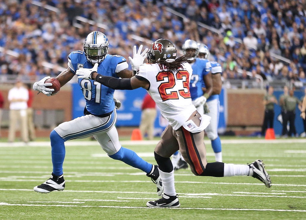 . Calvin Johnson #81 of the Detroit Lions makes the catch and runs for a first down as Mark Barron #23 of the Tampa Bay Buccanners attempts to make the stop during the second quarter of the game at Ford Field on November 24, 2013 in Detroit, Michigan.  (Photo by Leon Halip/Getty Images)