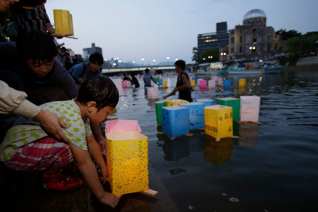 . A boy releases a paper lantern to the Motoyasu River with the backdrop of the Atomic Bomb Dome in Hiroshima, western Japan, Tuesday, Aug. 6, 2013.  (AP Photo/Shizuo Kambayashi)