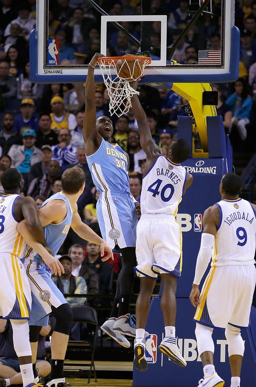 . Quincy Miller #30 of the Denver Nuggets dunks over Harrison Barnes #40 of the Golden State Warriors at ORACLE Arena on January 15, 2014 in Oakland, California.   (Photo by Ezra Shaw/Getty Images)