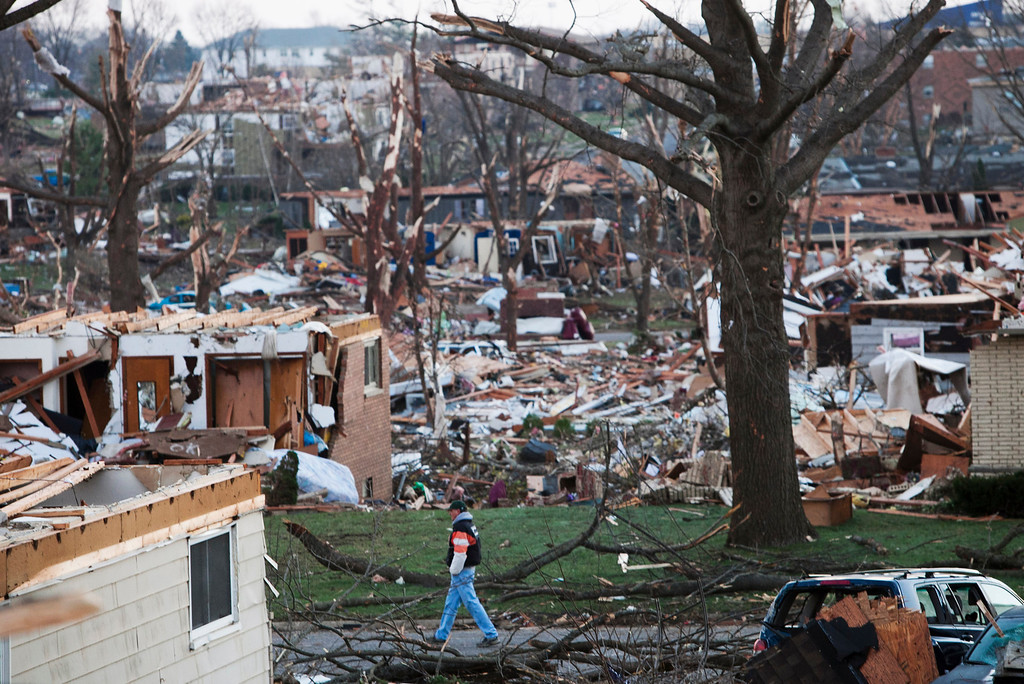 . A man walks through what is left of a neighborhood in Washington, Ill., on Monday, Nov. 18, 2013, a day after a tornado ripped through the central Illinois town. The tornado cut a path about an eighth of a mile wide from one side of Washington to the other and damaged or destroyed as many as 500 homes. (AP Photo/Armando Sanchez)