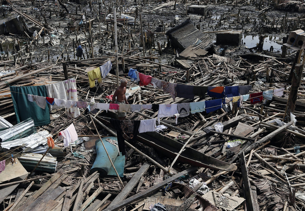 . A Filipino is surrounded by clothes drying and debris left by Typhoon Haiyan in Basey town of Eastern Samar Province, Philippines, 21 November 2013. EPA/ROLEX DELA PENA