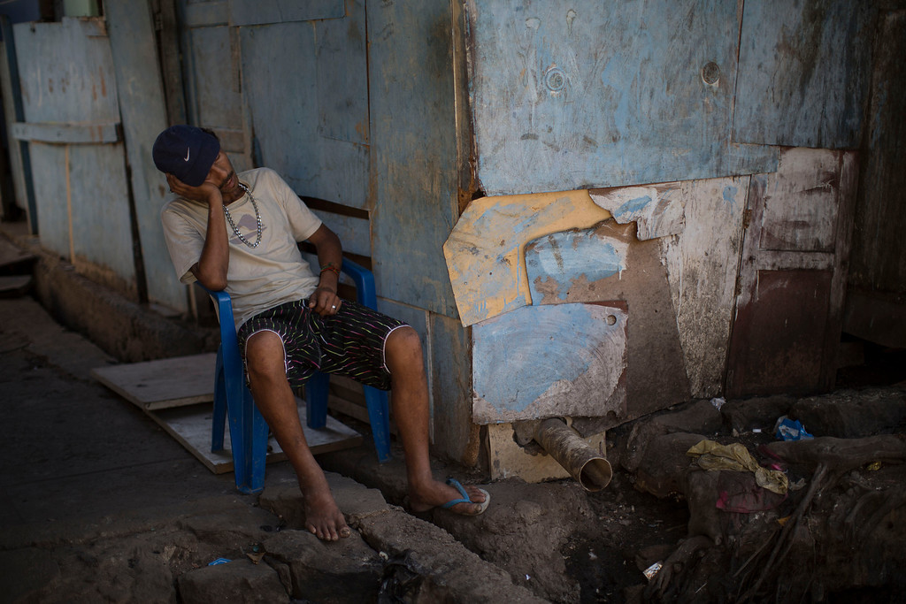 . A man naps outside his home in a poor area of the Mare slum complex in Rio de Janeiro, Brazil, Saturday, April 5, 2014. More than 2,000 Brazilian soldiers stormed into the slum complex Saturday with armored personnel carriers and helicopters in a bid to improve security two months before the start of the World Cup. (AP Photo/Felipe Dana)