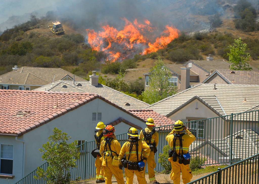 . Firefighters from Glendale, Calif., and Pasadena, Calif., stand watch as bulldozers clear a firebreak near a wildfire burning along a hillside near homes in Thousand Oaks, Calif., Thursday, May 2, 2013. (AP Photo/Mark J. Terrill)