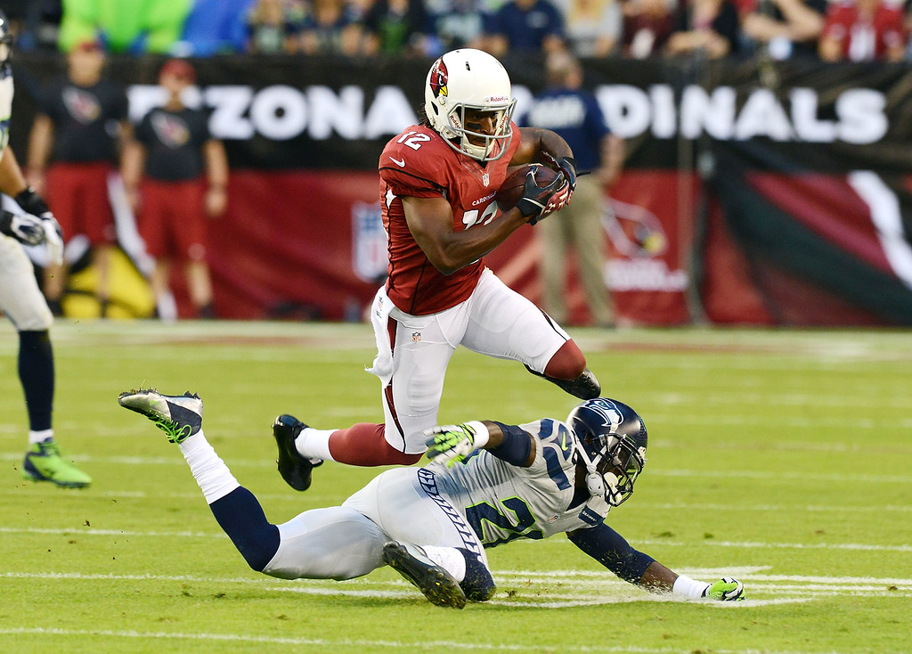 . GLENDALE, AZ - OCTOBER 17:  Andre Roberts #12 of the Arizona Cardinals jumps over a diving Jeremy Lane #20 of the Seattle Seahawks at University of Phoenix Stadium on October 17, 2013 in Glendale, Arizona.  (Photo by Norm Hall/Getty Images)