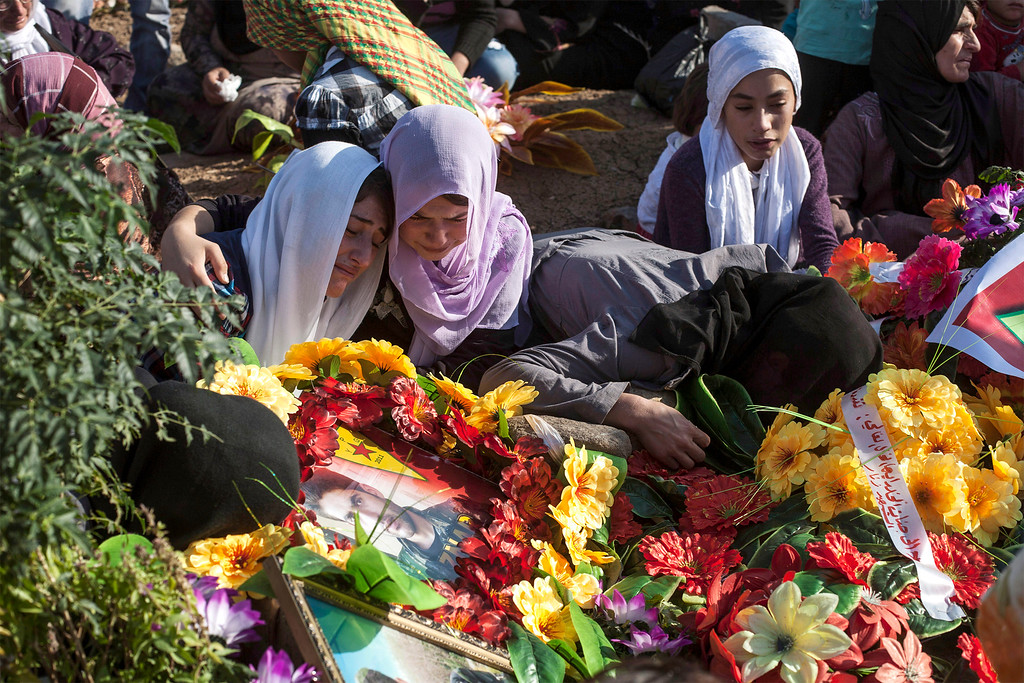 . Kurdish women grieve during a visit to the Martyrs\' cemetery to remember those who died in Syria\'s civil war on October 15, 2013, in the Syrian Kurdish town of Derik (al-Malikiyah in Arabic), on the first day of Eid al-Adha, which commemorates the willingness of Abraham to sacrifice his son at God\'s command.  AFP PHOTO/STR-/AFP/Getty Images
