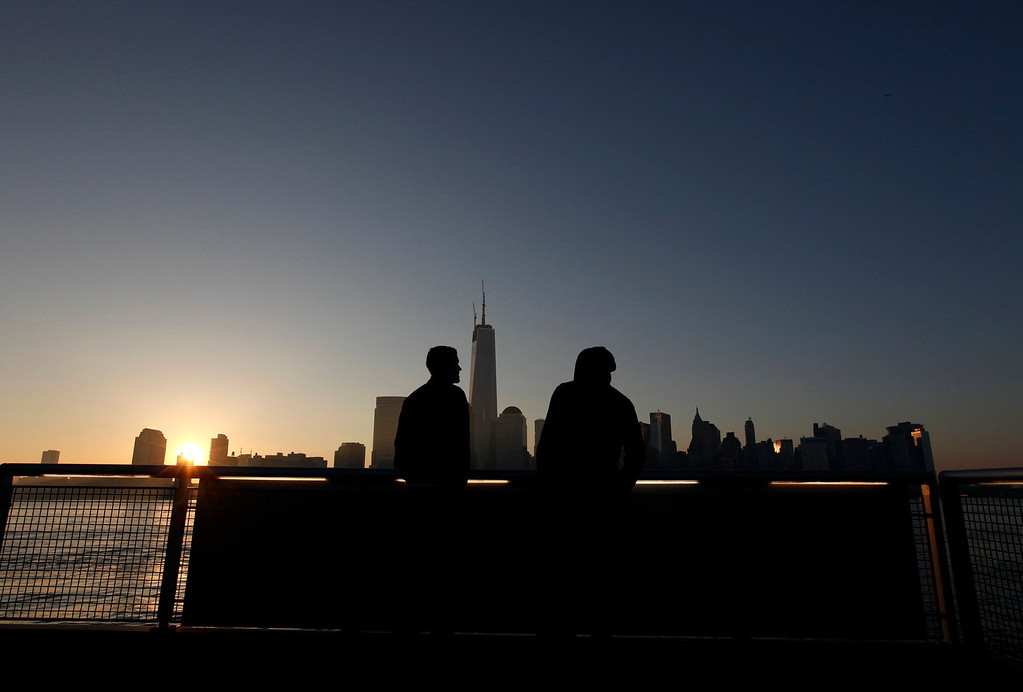 . Two people look out at One World Trade Center in New York as seen across the Hudson River in Jersey City, New Jersey, May 10, 2013. The final piece of the building\'s spire will be attached later this morning. REUTERS/Gary Hershorn