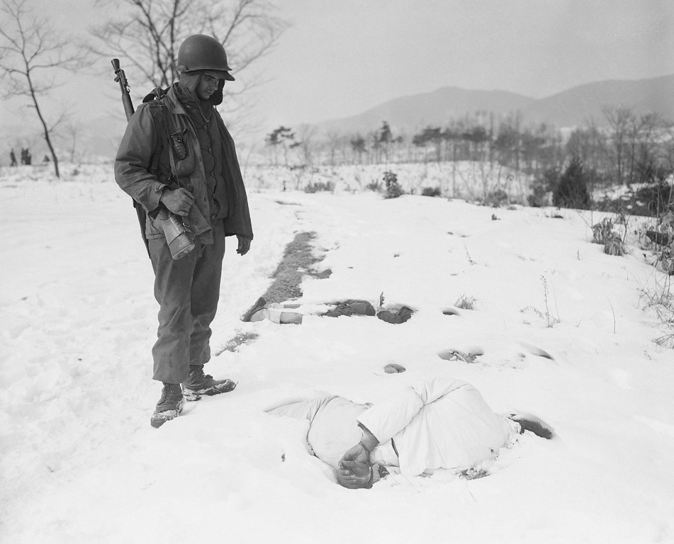 . Cpl. Clifford Rodgers, Muskogee, Okla., looks at bound wrist of a Korean Civilians found in deep snow on Jan. 27, 1951 near Yangji, about 15 miles northwest of Ichon on the central front. The atrocity victim, one of several found in the area, presumably had been killed by reds retreating before allied advance. (AP Photo/Max Desfor