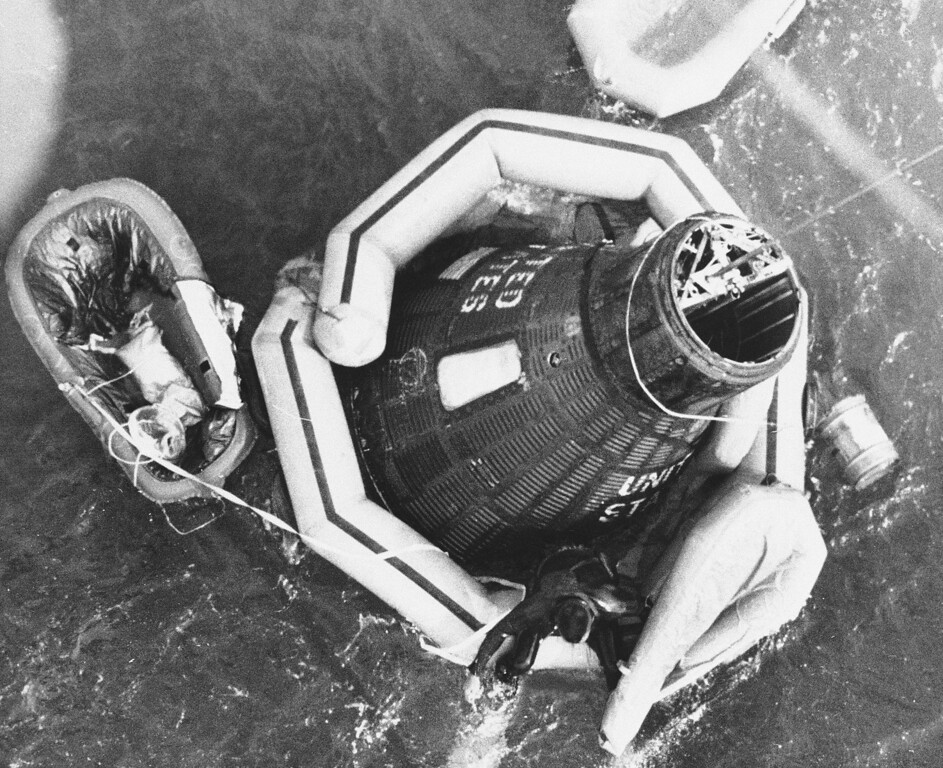 . A frogman attaches flotation gear to Aurora 7 capsule of Scott Carpenter after the astronaut splashed down in the ocean following three-orbit whirl from Cape Canaveral, Florida, May 24, 1962. (AP Photo)