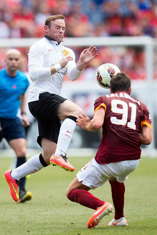 . Wayne Rooney #10 of Manchester United goes for the ball against Arturo Calabresi #91 of AS Roma during an exhibition match of the Guinness International Champions Cup at Sports Authority Field at Mile High on July 26, 2014, in Denver, Colorado. Manchester United won 3-2. (Photo by Daniel Petty/The Denver Post)