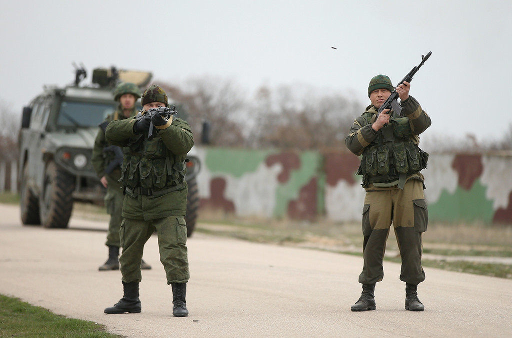 . Troops under Russian command fire weapons into the air and scream orders to turn back at an approaching group of over 100 hundred unarmed Ukrainian troops at the Belbek airbase, which the Russian troops are occupying, in Crimea on March 4, 2014 in Lubimovka, Ukraine. The Ukrainians are stationed at their garrison nearby, and after spending a tense night anticipating a Russian attack following the expiration of a Russian deadline to surrender, in which family members of troops spent the night at the garrison gate in support of the soldiers, their commander Colonel Yuli Mamchor announced his bold plan this morning to retake the airfield by confronting the Russian-lead soldiers unarmed. The Russian-lead troops fired their weapons into the air but then granted Mamchor the beginning of negotiations with their commander. Russian-lead troops have blockaded a number of Ukrainian military bases across Crimea.  (Photo by Sean Gallup/Getty Images)