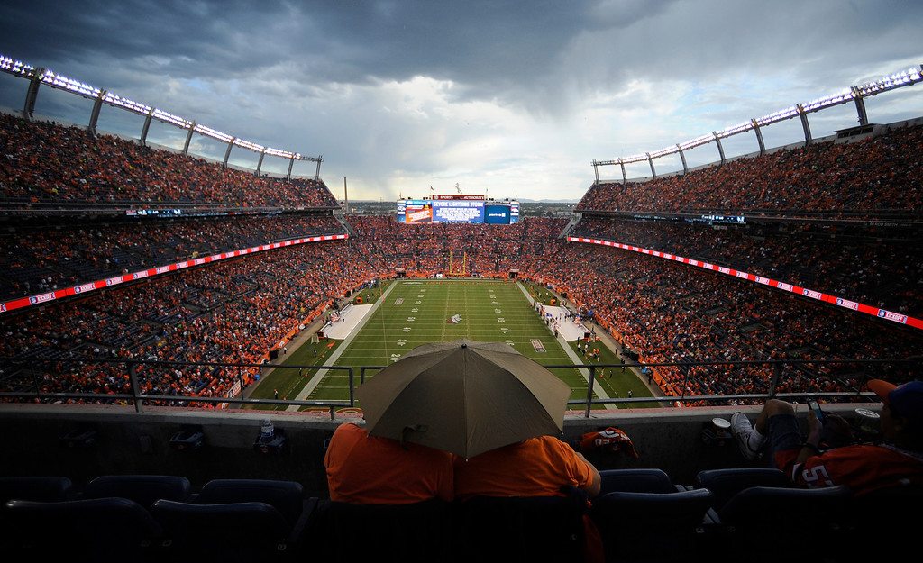 . DENVER, CO - SEPTEMBER 05: Phillip and Phyllis Aschenbrenner take cover from the rain before the start of the game. The Denver Broncos took on the Baltimore Ravens in the first game of the 2013 season at Sports Authority Field at Mile High in Denver on September 5, 2013. (Photo by AAron Ontiveroz/The Denver Post)