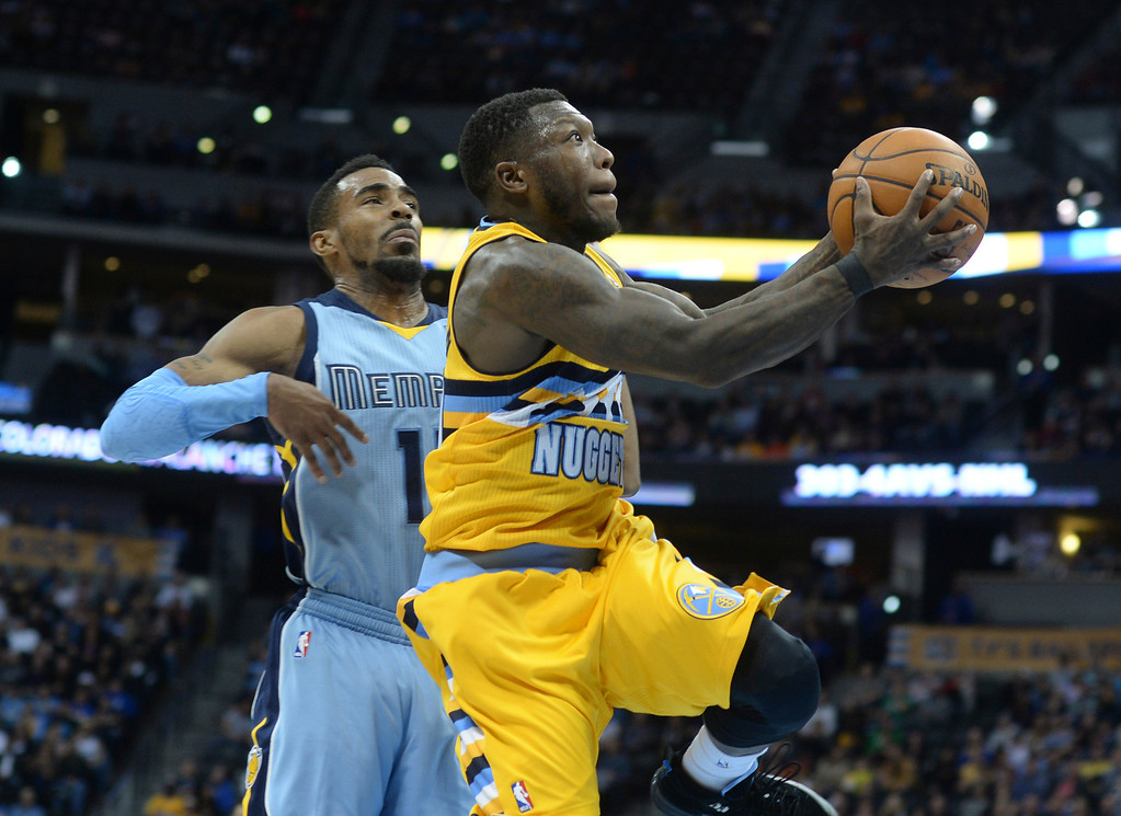 . DENVER, CO. - JANUARY 03:  Denver Nuggets guard Nate Robinson (4) drove past Memphis guard Mike Conley (11) for a bucket in the fourth quarter. The Denver Nuggets broke an eight-game losing streak with a 111-108 win over the Memphis Grizzlies at the Pepsi Center Friday night, January 3, 2014. Photo By Karl Gehring/The Denver Post