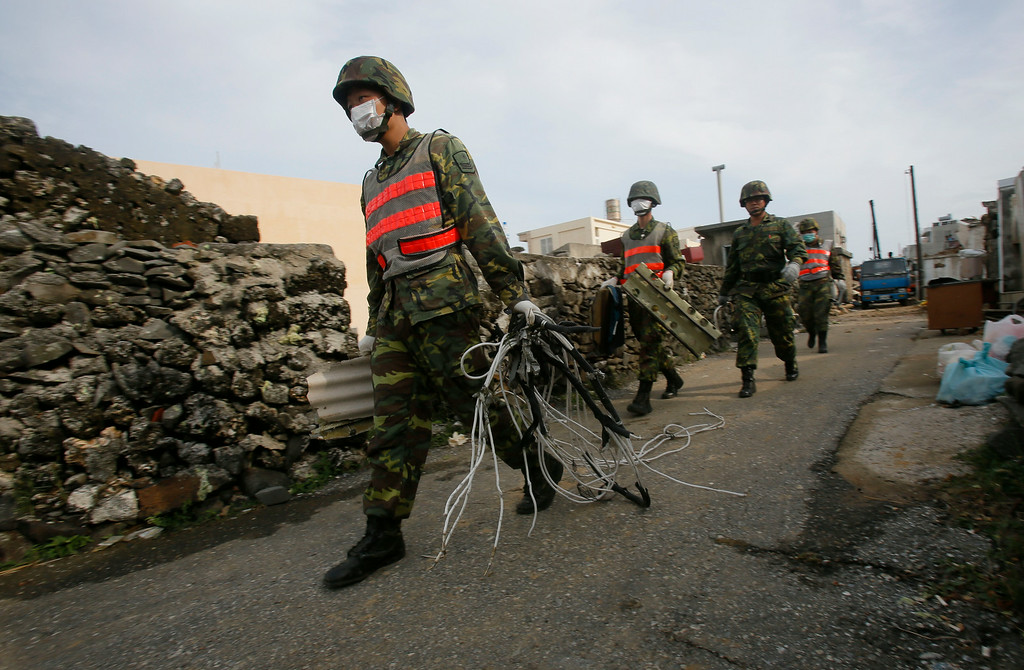 . Soldiers remove debris from the scene of crashed TransAsia Airways Flight GE222 on the outlying island of Penghu, Taiwan, Thursday, July 24, 2014. (AP Photo/Wally Santana)