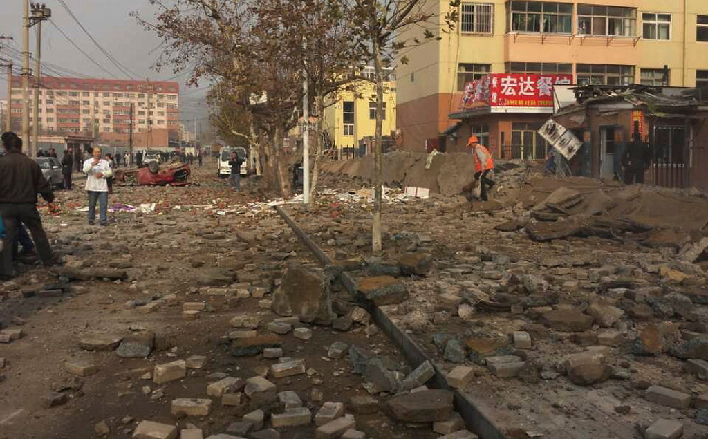 . People walk on a damaged street after a pipeline explosion in Qingdao in east China\'s Shandong province Friday, Nov. 22, 2013. Leaked oil from a ruptured oil pipe, owned by China\'s largest oil refiner, Sinopec, caught fire and exploded Friday in an eastern Chinese port city, killing and injuring many people. (AP Photo)