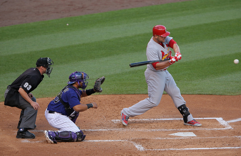 . Matt Holliday #7 of the St. Louis Cardinals hits an RBI double to score Mark Ellis #3 of the St. Louis Cardinals as catcher Wilin Rosario #20 of the Colorado Rockies backs up the plate and umpire Will Little oversees the action as the Cards take a 1-0 lead in the third inning at Coors Field on June 23, 2014 in Denver, Colorado.  (Photo by Doug Pensinger/Getty Images)