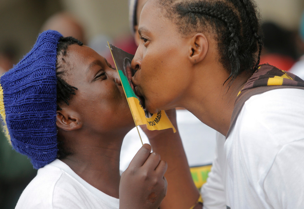 . Two women  kiss the flag bearing the portrait of Nelson Mandela at his memorial service  at  the FNB stadium in  Johannesburg, South Africa, Tuesday, Dec. 10, 2013. Mandela died Thursday at his Johannesburg home after a long illness. He was 95(AP Photo/Tsvangirayi Mukwazhi)