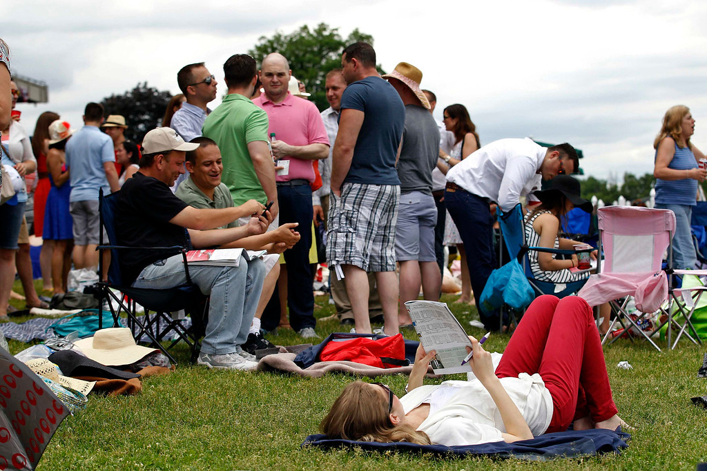. A fan looks over a racing program while lying amongst the crowd ahead of the 145th running of the Belmont Stakes, the final leg of horse racing\'s triple crown, at Belmont Park in Elmont, New York, June 8, 2013.      REUTERS/Adam Hunger
