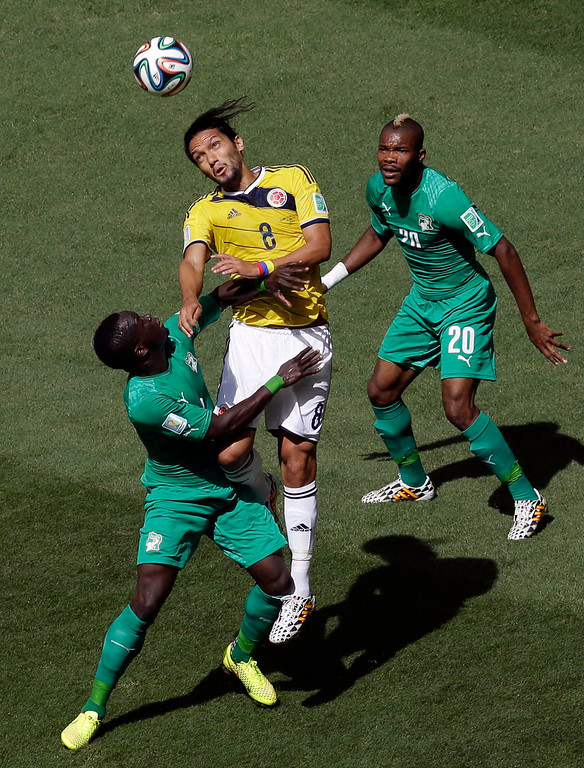. Colombia\'s Abel Aguilar, center goes for a header with Ivory Coast\'s Arthur Boka as Ivory Coast\'s Serey Die, right,  looks on during the group C World Cup soccer match between Colombia and Ivory Coast at the Estadio Nacional in Brasilia, Brazil, Thursday, June 19, 2014.  (AP Photo/Themba Hadebe)