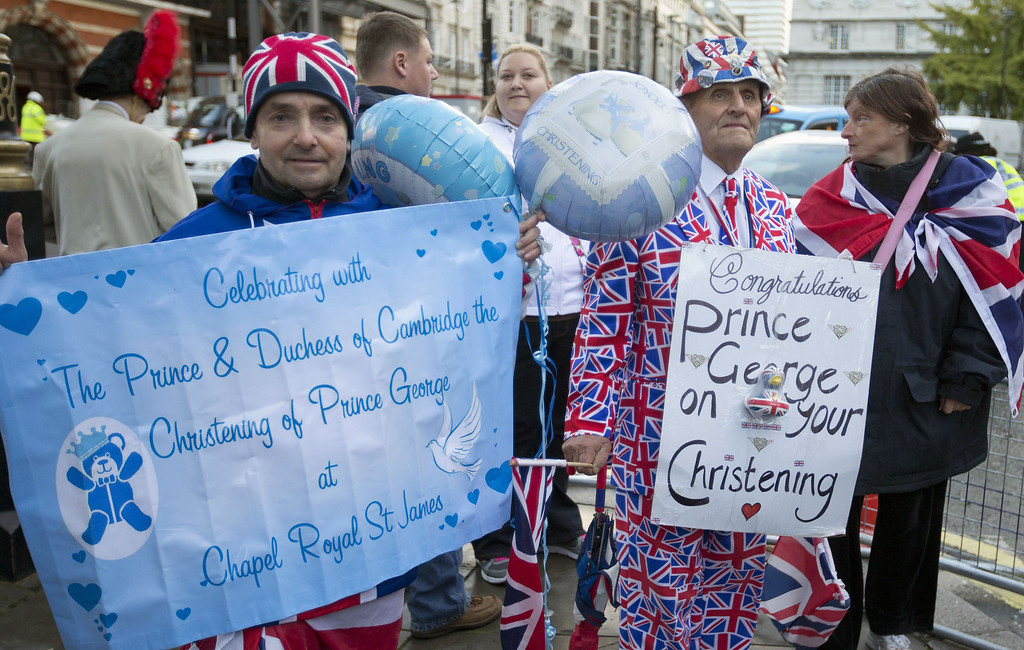 . Royal well-wishers gather and display their home made placards and greetings to the media,  as they wait outside St James\'s Palace, for the christening of Britain\'s Prince George, in London, Wednesday, Oct. 23, 2013.  (AP Photo/Alastair Grant)