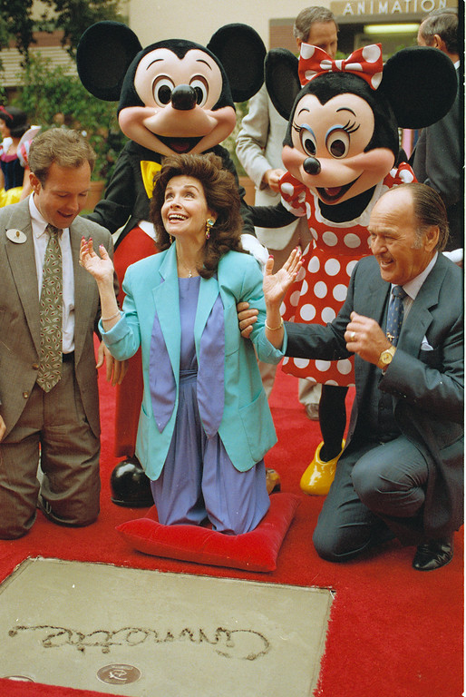 ". Former ""Mouseketeer\"" Annette Funicello gets set to put her hands in the cement at Walt Disney Studios Theatre, in Burbank, Calif., as she is honored with the Disney Legend Award, on October 21, 1992. With Funicello is her husband Glen Holt, right, and Jeff Hofman, left, Disney Studios official. (AP Photo/Nick Ut)"