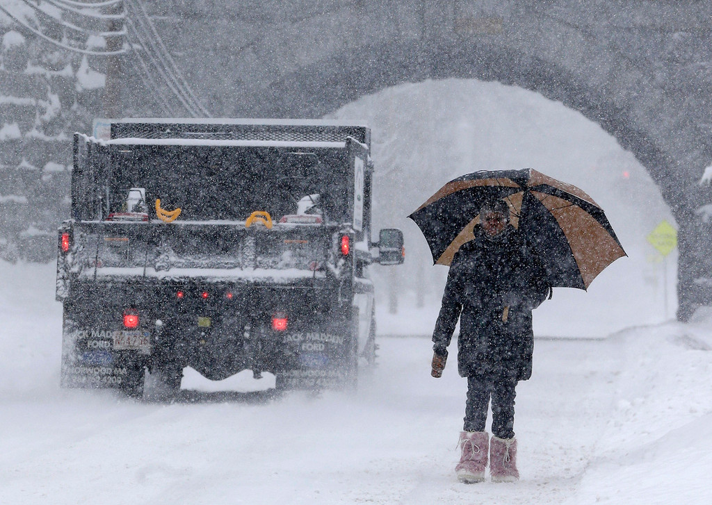 . Trishia Williams, of Norwood, Mass., uses an umbrella while making her way to work on a snowy road in Norwood, Wednesday, Feb. 5, 2014.  Six to 12 inches of snow is expected around Boston, with 3 to 6 inches in southeastern areas before changing to sleet and rain Wednesday. (AP Photo/Steven Senne)