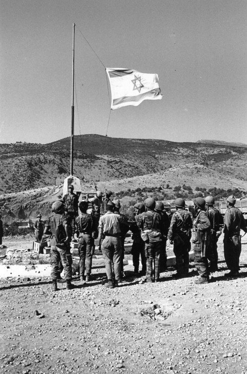 . 12th June 1967:  Israeli troops salute their flag as they occupy Syrian territory during the Six Day War.  (Photo by Stan Meagher/Express/Getty Images)