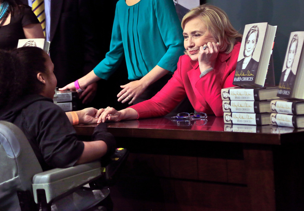. HiIlary Rodham Clinton, right, listens before signing a copy of her new book for a wheelchair-bound woman on Tuesday June 10, 2014, at Barnes and Noble bookstore in New York.    (AP Photo/Bebeto Matthews)