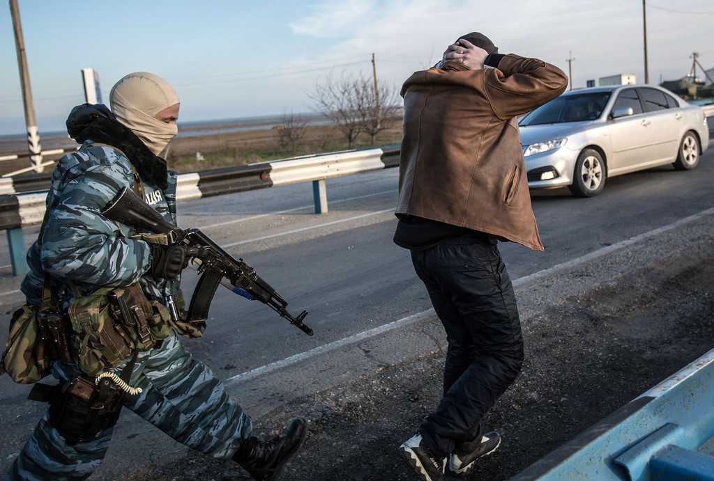 . A man holds his hands on his head as he is searched by pro-Russian servicemen at Chongar checkpoint blocking the entrance to Crimea on March 10, 2014. Russia vowed on March 10 to unveil its own solution to the Ukrainian crisis that would run counter to US efforts and would appear to leave room for Crimea to switch over to Kremlin rule. The unexpected announcement came as Ukraine\'s new pro-European leaders raced to rally Western support in the face of the seizure by Kremlin-backed forces of the strategic Black Sea peninsula and plans to hold a Sunday referendum on switching Crimea\'s allegiance from Kiev to Moscow. ALISA BOROVIKOVA/AFP/Getty Images