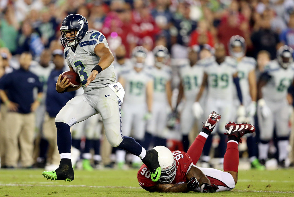 . GLENDALE, AZ - OCTOBER 17: Quarterback Russell Wilson #3 of the Seattle Seahawks avoids a tackle by defensive end Darnell Dockett #90 of the Arizona Cardinals during a game at the University of Phoenix Stadium on October 17, 2013 in Glendale, Arizona.  (Photo by Christian Petersen/Getty Images)