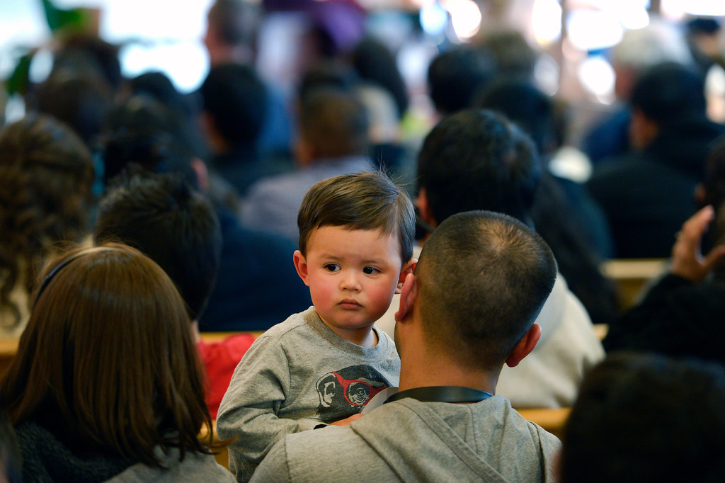 . AURORA, CO- FEBRUARY 9: Mateo Flores, 2, peers over his father Juan Flores\' shoulder, during the public meeting.  TOGETHER COLORADO held a public meeting  to talk about the United States immigration policies at St. Therese Catholic Church, 1243 Kingston Street in Aurora, Co  on February 9th, 2013.   Colorado State Senator Michael Bennet, and Colorado Representatives Mike Coffman and Jared Polis attended and spoke at the meeting.  The organization wanted to tell the state\'s representatives why they want a road map to citizenship for 11 million aspiring Americans.  More than 800 faith and community leaders packed the small church in Aurora. (Photo By Helen H. Richardson/ The Denver Post)