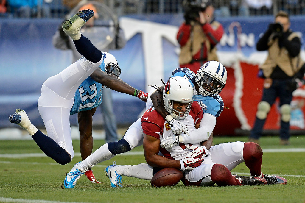 Description of . Arizona Cardinals wide receiver Larry Fitzgerald (11) can't hang onto a pass as he is defended by Tennessee Titans cornerback Jason McCourty (30) and safety Bernard Pollard (31) in the second quarter of an NFL football game Sunday, Dec. 15, 2013, in Nashville, Tenn. (AP Photo/Mark Zaleski)