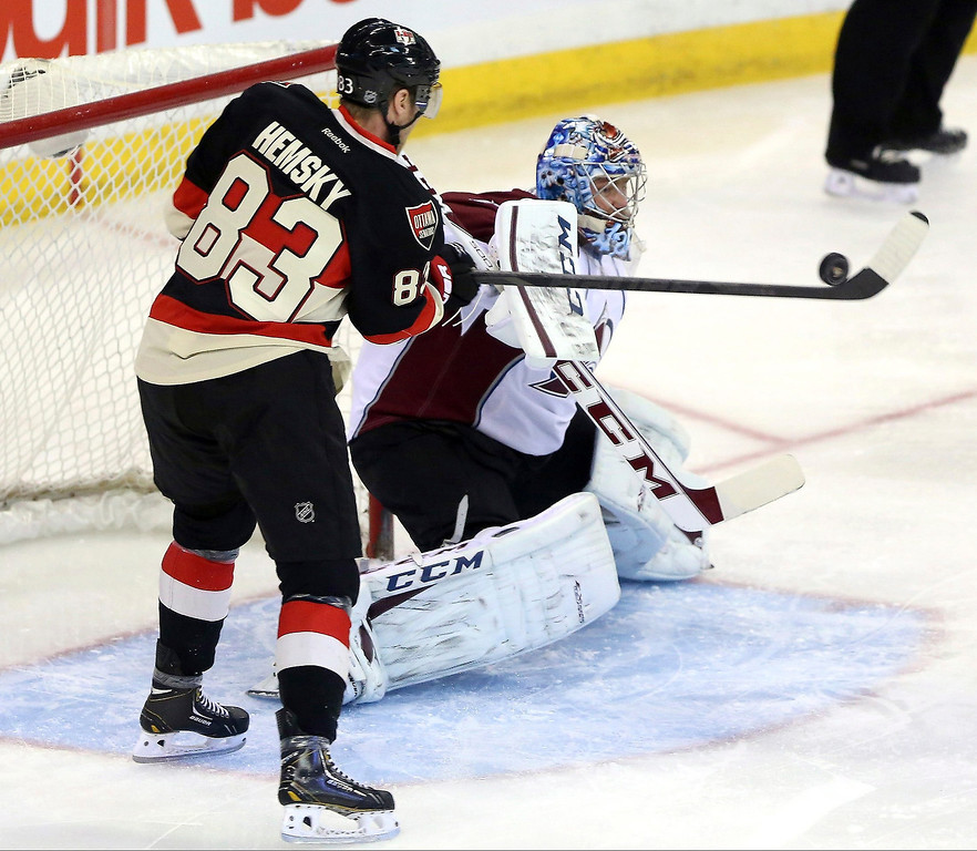 . Ottawa Senators\' Ales Hemsky (83) attempts to bat the puck past Colorado Avalanche goaltender Semyon Varlamov (1) during first-period NHL hockey game action in Ottawa, Ontario, Sunday March 16, 2014. (AP Photo/The Canadian Press, Fred Chartrand)