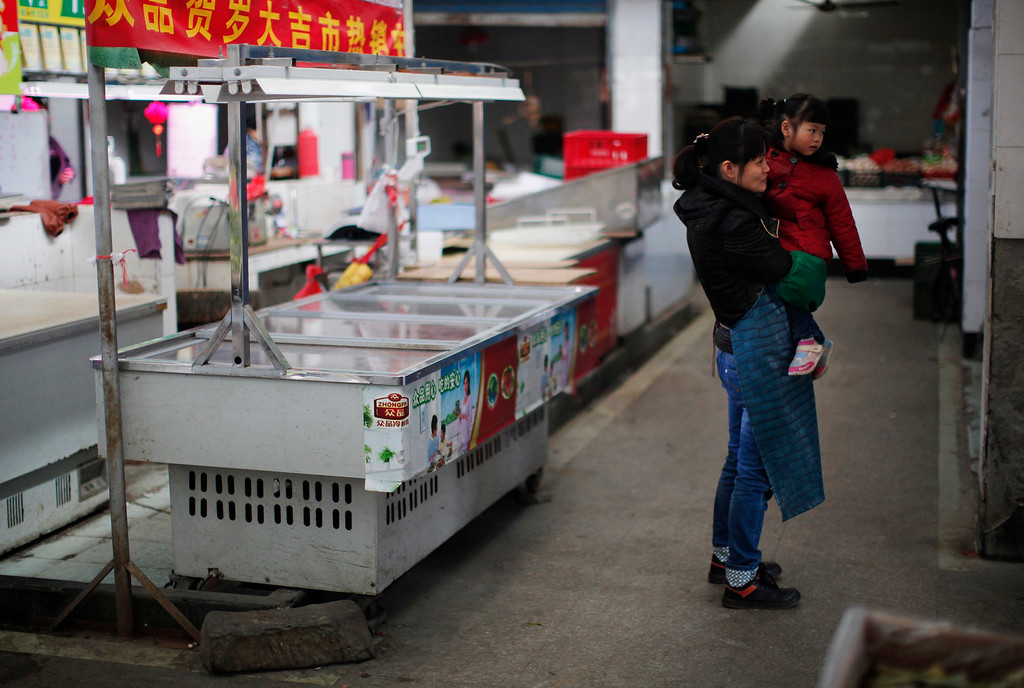 . A woman and her daughter stand in front of a closed butcher stall at a local market in Minhang district, south of Shanghai April 3, 2013. According to vendors in the area, the stall belongs to a 27 year-old man who died last month after contracting a strain of avian influenza that had never been passed to humans before. China reported four new cases on Tuesday of a strain of bird flu that was previously unknown in humans but has already killed two people, raising the total of known cases to seven. The World Health Organisation (WHO) said on Monday there was no evidence that the H7N9 strain could be transmitted between people, but that it was investigating the outbreak. The four new patients in China\'s eastern Jiangsu province were all in critical condition and receiving emergency treatment, the Xinhua News Agency said, citing the Jiangsu provincial health bureau. A woman in Anhui province who caught the virus in early March is also in critical condition. REUTERS/Carlos Barria