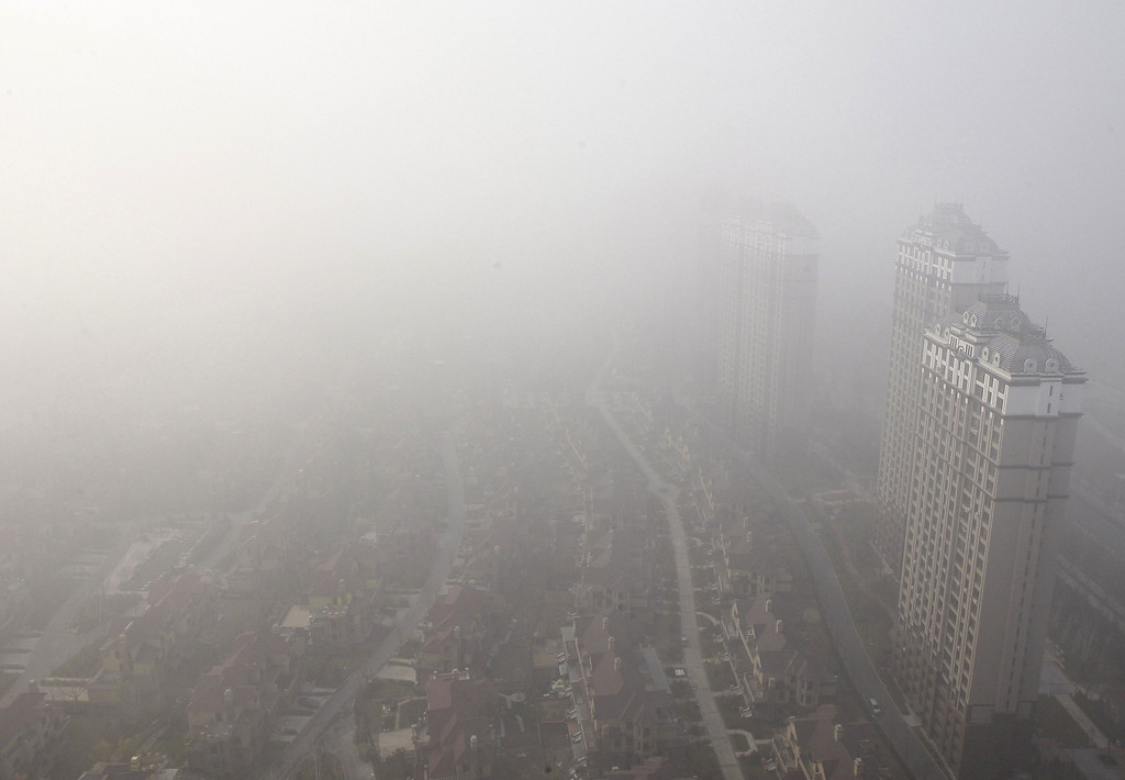 . Buildings and streets are seen under heavy smog in Harbin, northeast China\'s Heilongjiang province on October 22, 2013. Thick smog enveloped a major Chinese city for a third day on October 22, with schools and a regional airport shut and poor visibility forcing ground transport to a halt in places.   AFP PHOTOSTR/AFP/Getty Images