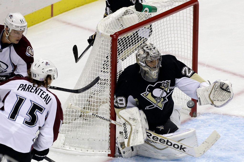 . Pittsburgh Penguins goalie Marc-Andre Fleury (29) gloves the puck before Colorado Avalanche\'s P.A. Parenteau (15) and Jamie McGinn (11) can get a stick on it in the first period of an NHL hockey game in Pittsburgh Monday, Oct. 21, 2013. (AP Photo/Gene J. Puskar)