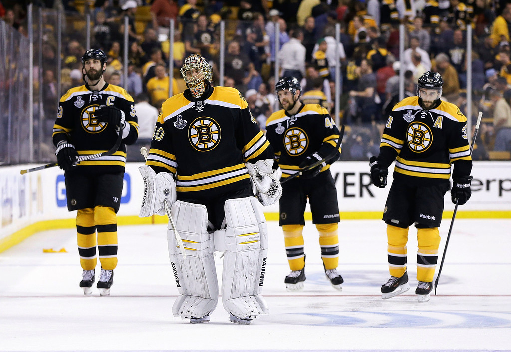 . Boston Bruins defenseman Zdeno Chara (33), of Slovakia, Boston Bruins goalie Tuukka Rask (40), of Finland, Boston Bruins defenseman Dennis Seidenberg (44), of Germany, and Boston Bruins center Patrice Bergeron (37) leave the ice after their 6-5 loss to the Chicago Blackhawks during the first overtime period in Game 4 of the NHL hockey Stanley Cup Finals, Wednesday, June 19, 2013, in Boston. Chicago won 6-5.(AP Photo/Elise Amendola)