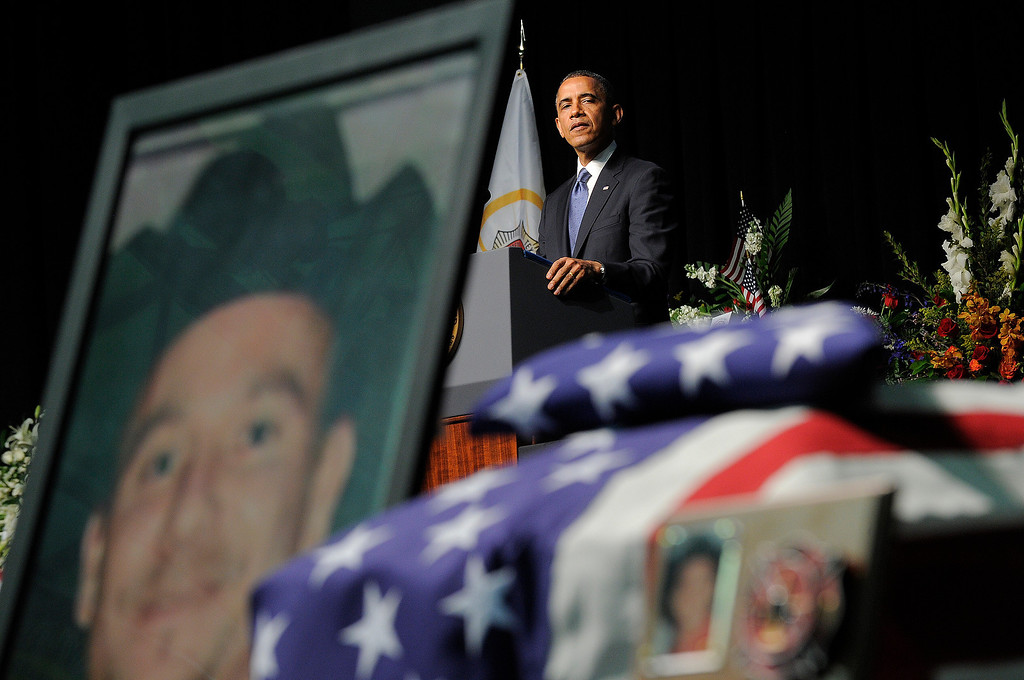 . Caskets and pictures of firefighters are seen as US President Barack Obama (C-back) speaks during a memorial service at Baylor University in Waco, Texas, on April 25, 2013 for the firefighters who were killed in a huge blast at a Texas fertilizer plant last week. . AFP PHOTO/Jewel  SAMAD/AFP/Getty Images