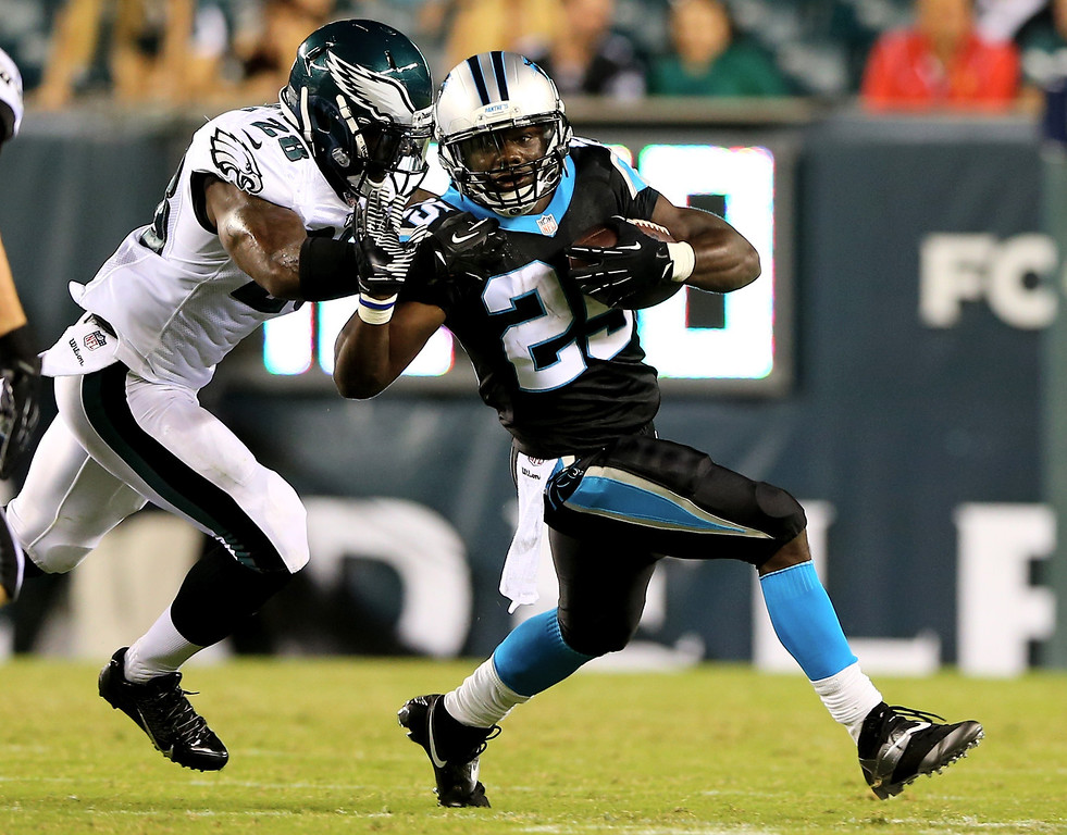. PHILADELPHIA, PA - AUGUST 15:  Kenjon Barner #25 of the Carolina Panthers carries the ball as Earl Wolff #28 of the Philadelphia Eagles defends on August 15, 2013 at Lincoln Financial Field in Philadelphia, Pennslyvania.  (Photo by Elsa/Getty Images)