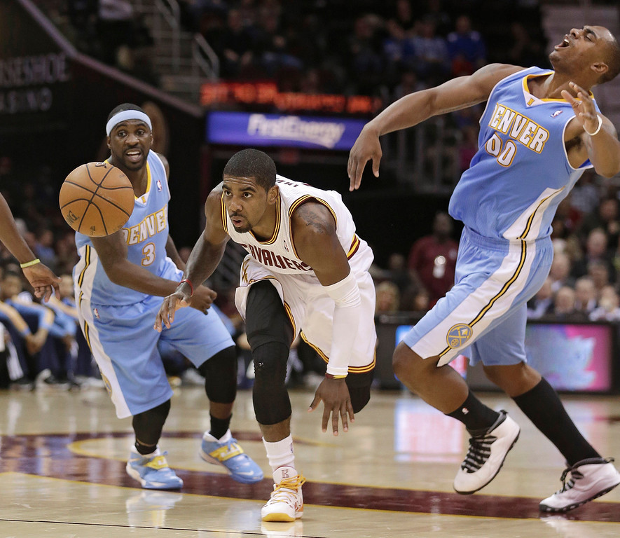 . Cleveland Cavaliers\' Kyrie Irving, center, gets between Denver Nuggets\' Ty Lawson (3) and Darrell Arthur (00) during the first quarter of an NBA basketball game on Wednesday, Dec. 4, 2013, in Cleveland. (AP Photo/Tony Dejak)
